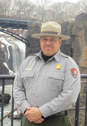 Ernie Hernandez in park ranger garb standing in front of the Great Falls.