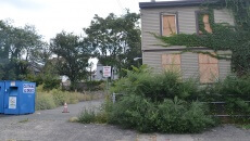 Site of the former liquor store and the damaged two-family home that remains standing.