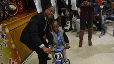 Councilman William McKoy with a boy who won a bicycle through the raffle.