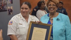 Deputy chief Lourdes Phelan, left, and mayor Jane Willaism-Warren, right, holding a proclamation recognizing  Phelan for breaking the department's glass ceiling.