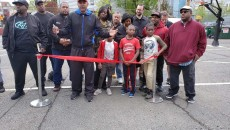 Willie Peterkin, pictured holding scissors, during ribbon cutting at new basketball courts on Saturday.