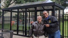 Priestly and Velez posing for a photograph in front of the new bus shelter.