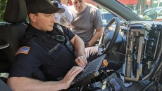 Police officer Buchanan shows reporters the  terminal inside a police unit.