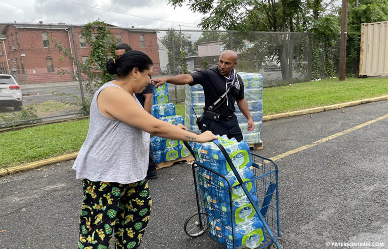 Firefighter Brandy Acosta handing out water to Paterson resident Yosemis Baldayac De Lopez at Eastside High School on Thursday.