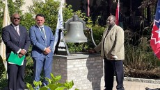 Historian Jimmy Richardson rings the Freedom Bell on Tuesday. Mayor Andre Sayegh and Dwayne Cox, president of the Paterson Parking Authority, look on.